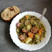 Ragoût de légumes, salade, pommes de terre, carottes, oignon, petits pois et saucisses de Montbéliard.